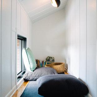 Exemple d'une chambre neutre rétro avec un mur blanc et un sol en bois brun.