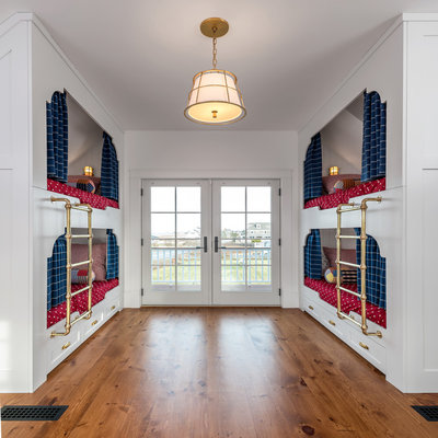 Inspiration for a coastal gender-neutral medium tone wood floor kids' room remodel in Portland Maine with white walls