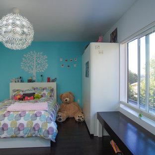 Ejemplo de dormitorio infantil de 4 a 10 años, moderno, de tamaño medio, con paredes azules y suelo de madera oscura