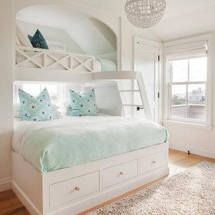 Maritim inredning av ett flickrum kombinerat med sovrum och för 4-10-åringar, med vita väggar, ljust trägolv och beiget golv