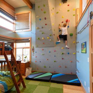 Cette photo montre une chambre d'enfant tendance avec un sol en bois brun et un mur bleu.