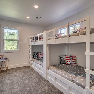 Immagine di una piccola cameretta per bambini da 4 a 10 anni american style con pareti bianche, moquette e pavimento grigio