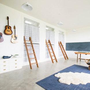 Foto på ett stort lantligt könsneutralt barnrum kombinerat med sovrum, med vita väggar, betonggolv och grått golv