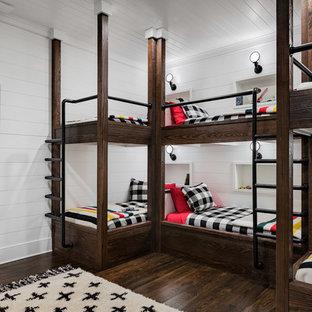 Réalisation d'une grande chambre d'enfant champêtre avec un mur blanc, un sol en bois foncé et un sol marron.
