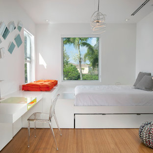 Example of a minimalist gender-neutral medium tone wood floor kids' room design in Miami with white walls