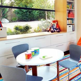 Foto på ett litet funkis könsneutralt barnrum kombinerat med lekrum och för 4-10-åringar, med beige väggar och mellanmörkt trägolv