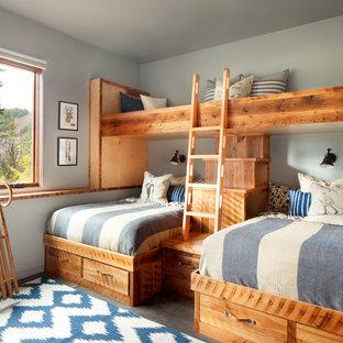 Bild på ett mellanstort rustikt könsneutralt barnrum kombinerat med sovrum, med betonggolv, grå väggar och grått golv
