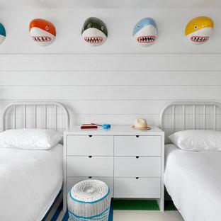 Inredning av ett maritimt könsneutralt barnrum kombinerat med sovrum och för 4-10-åringar, med vita väggar, heltäckningsmatta och flerfärgat golv