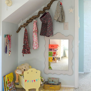 Trendy girl carpeted kids' room photo in New York with blue walls