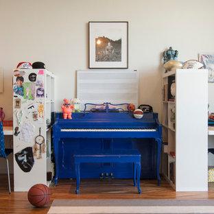 Immagine di una grande cameretta per bambini design con pareti bianche e pavimento in legno massello medio