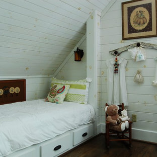 Example of a mountain style gender-neutral dark wood floor kids' room design in New York with white walls