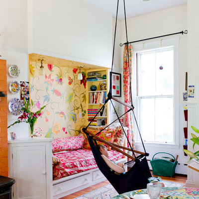 Eclectic girl medium tone wood floor kids' room photo in Boston with multicolored walls