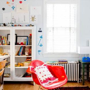 Esempio di una cameretta per bambini da 4 a 10 anni eclettica con pareti blu e pavimento in legno massello medio