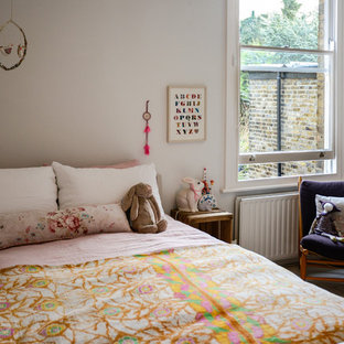 Example of a danish girl painted wood floor kids' bedroom design in London with white walls