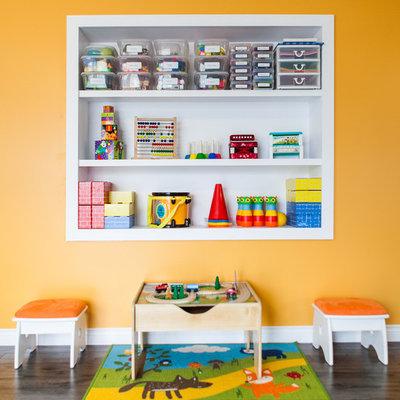 Trendy gender-neutral dark wood floor kids' room photo in Other with orange walls
