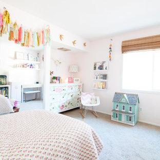 Immagine di una cameretta per bambini da 4 a 10 anni eclettica di medie dimensioni con pareti rosa