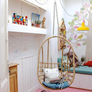 Skandinavisk inredning av ett flickrum kombinerat med lekrum, med vita väggar, målat trägolv och rosa golv