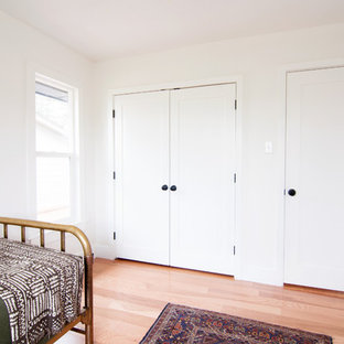 Mid-sized midcentury modern gender-neutral light wood floor kids' room photo in Denver with white walls