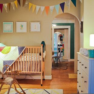 Imagen de habitación infantil unisex clásica con suelo de madera en tonos medios