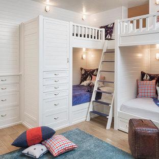 Coastal medium tone wood floor kids' bedroom photo in Orange County with white walls