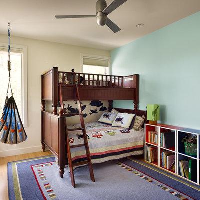 Transitional boy medium tone wood floor kids' room photo in Austin with blue walls