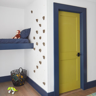 Inspiration for a beach style boy medium tone wood floor playroom remodel in Manchester with white walls
