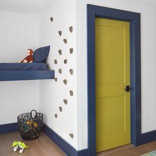 Ispirazione per una cameretta per bambini da 4 a 10 anni stile marino con pareti bianche e pavimento in legno massello medio