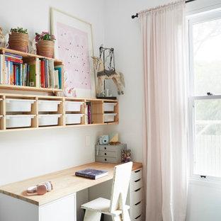 Esempio di una cameretta per bambini da 4 a 10 anni nordica di medie dimensioni con pareti bianche, pavimento in cemento e pavimento grigio