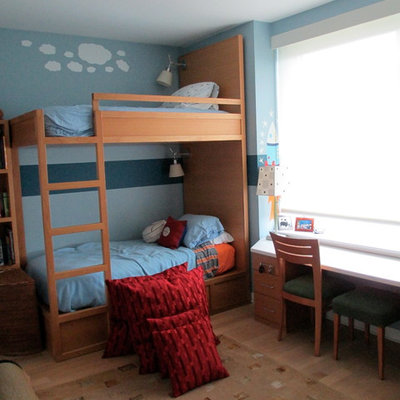 Small elegant boy light wood floor kids' bedroom photo in New York with blue walls