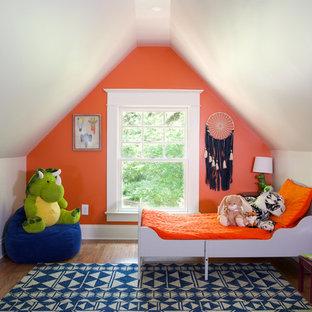 Inredning av ett klassiskt mellanstort barnrum kombinerat med sovrum, med orange väggar, mellanmörkt trägolv och brunt golv