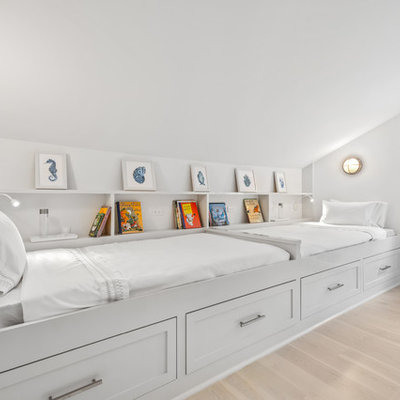 Example of a beach style gender-neutral light wood floor and beige floor kids' room design in New York with white walls