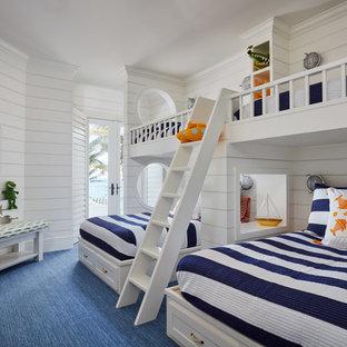 Inspiration för ett maritimt barnrum kombinerat med sovrum och för 4-10-åringar, med vita väggar, heltäckningsmatta och blått golv