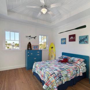 Cette photo montre une chambre d'enfant de 4 à 10 ans exotique avec un mur blanc et un sol en bois brun.
