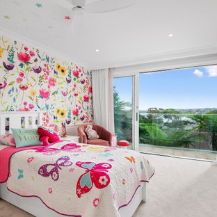 Photo of a large beach style kids' bedroom for kids 4-10 years old and girls in Sydney with multi-coloured walls, carpet, pink floor and wallpaper.