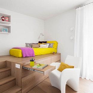 Esempio di una grande cameretta per bambini da 4 a 10 anni minimal con pareti bianche e pavimento in legno massello medio