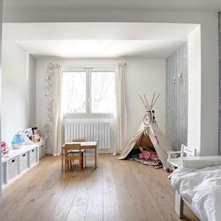 Cette image montre une chambre de fille de 1 à 3 ans nordique avec un mur blanc, un sol en bois brun et un sol marron.
