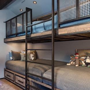 Inspiration för ett litet rustikt könsneutralt barnrum kombinerat med sovrum och för 4-10-åringar, med grå väggar och mellanmörkt trägolv