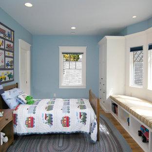 Réalisation d'une chambre d'enfant craftsman avec un mur bleu, un sol en bois brun et un sol marron.