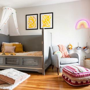 Mid-sized trendy girl medium tone wood floor and brown floor kids' room photo in Boston with gray walls