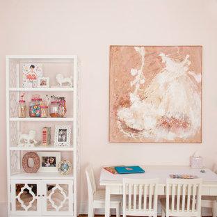 Immagine di una cameretta per bambini da 4 a 10 anni boho chic con pareti rosa e pavimento in legno massello medio