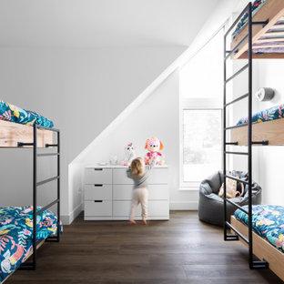 Cette image montre une chambre d'enfant design avec un mur blanc, un sol en bois foncé, un sol marron et un plafond voûté.