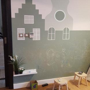 Modern inredning av ett litet könsneutralt småbarnsrum kombinerat med lekrum, med gröna väggar