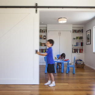 Design ideas for a contemporary gender neutral kids' room in San Francisco with white walls and medium hardwood flooring.
