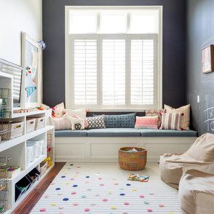 Klassisk inredning av ett mellanstort könsneutralt barnrum kombinerat med lekrum och för 4-10-åringar, med svarta väggar, mörkt trägolv och brunt golv
