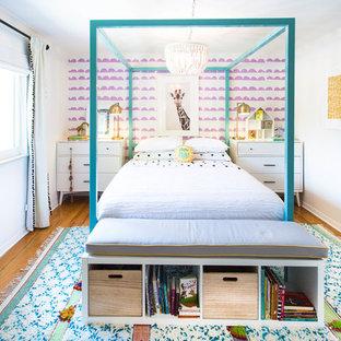 Inredning av ett modernt flickrum kombinerat med sovrum, med vita väggar, mellanmörkt trägolv och brunt golv