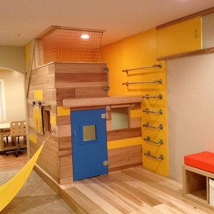 Esempio di una grande cameretta per bambini da 4 a 10 anni eclettica con pareti beige e pavimento in legno massello medio