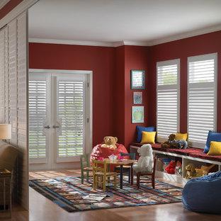 Exempel på ett mellanstort modernt könsneutralt barnrum kombinerat med lekrum och för 4-10-åringar, med röda väggar och ljust trägolv