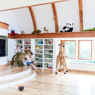 Esempio di una cameretta per bambini da 4 a 10 anni american style di medie dimensioni con pareti bianche e parquet chiaro