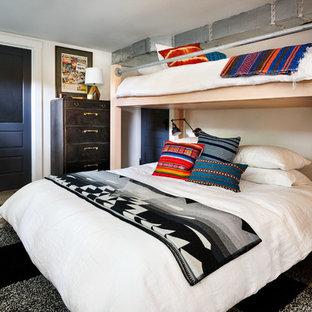 Inredning av ett eklektiskt könsneutralt barnrum kombinerat med sovrum, med vita väggar, betonggolv och grått golv