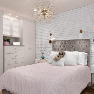 Immagine di una piccola cameretta per bambini design con pareti rosa, parquet chiaro e pavimento marrone